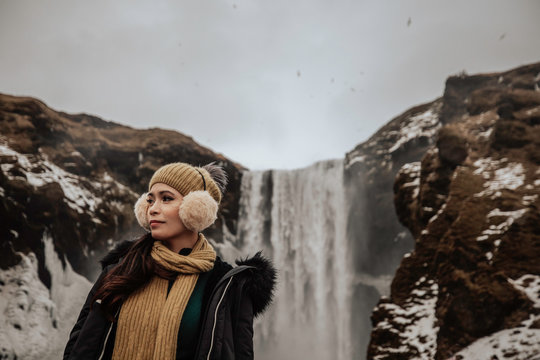 a pretty asian Filipina girl standing in front of a waterfall during winter time in Iceland on a cold and cloudy day while wearing her earmuffs and beanie hat with a yellow scarf and jacket