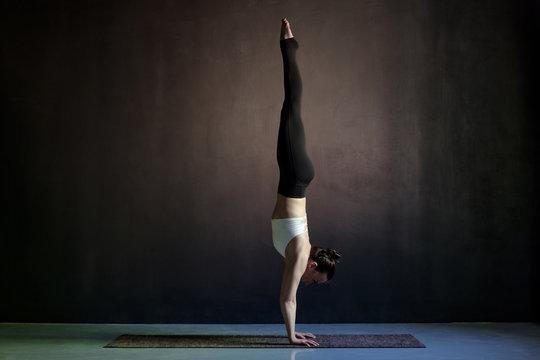 woman practicing yoga, Adho Mukha Vrksasana exercise, Downward facing Tree pose
