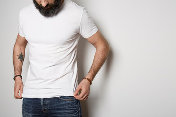 Attractive brutal tattooed bearded guy poses in blue jeans and blank gray t-shirt premium summer cotton, on white background. Mockup Copy Paste Advertisement