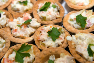Fish and meat salads in tartlets on a plate.