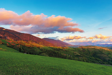 beautiful rural landscape in mountains at dawn. agricultural fields on hills. ridge in the distance. wonderful european countryside in springtime. gorgeous sky with red clouds.