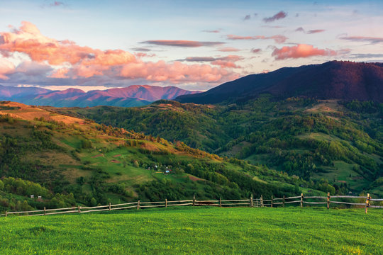 beautiful rural area in mountains at sunset. agricultural fields on hills. ridge in the distance. fence along the pasture. wonderful carpathian countryside in springtime. blue sky with red clouds.