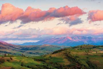 beautiful rural landscape in mountains at dawn. distant ridge with snowy tops behind the agricultural area. wonderful european countryside in springtime. sky with red clouds.