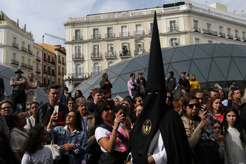 "People take pictures of penitents during the procession of ""La Soledad"" brotherhood during Holy Week in Madrid"