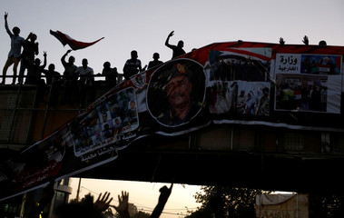 Protesters tear down a banner with a picture of Sudan's head of transitional council, Lieutenant General Abdel Fattah Al-Burhan Abdelrahman and pictures showing the Sudanese soldiers and protesters together, in Khartoum
