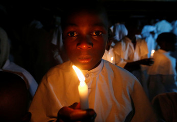 A Christian faithful of the Legio Maria African Mission church holds a candle as he attends the Easter vigil mass in their church in Fort Jesus area of Nairobi