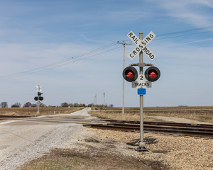railroad crossing with warning sign and lights in countryside with a gravel road