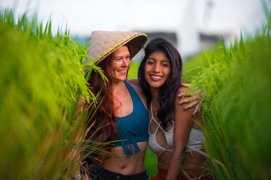 beautiful latin girl and her attractive red hair girlfriend both women enjoying Summer holidays together on rice field smiling happy playing with Asian traditional hat