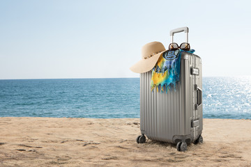 View of gray suitcase with pareo and hat on tropical  beach