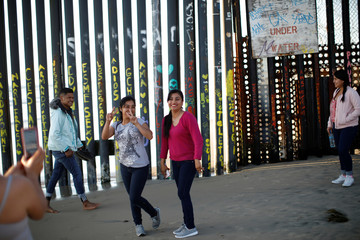 Two women pose for a picture at the beach near the border fence between the U.S. and Mexico in Tijuana
