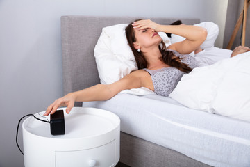 Woman Sleeping On Bed Turning Off Alarm Clock