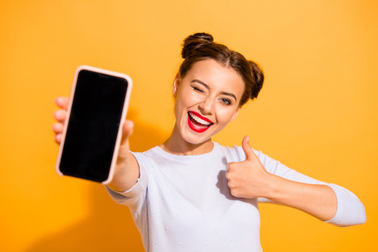 Close up photo of charming beautiful attractive lady offering suggesting recommending product raising her thumb up dressed up white sweater isolated over vivid background