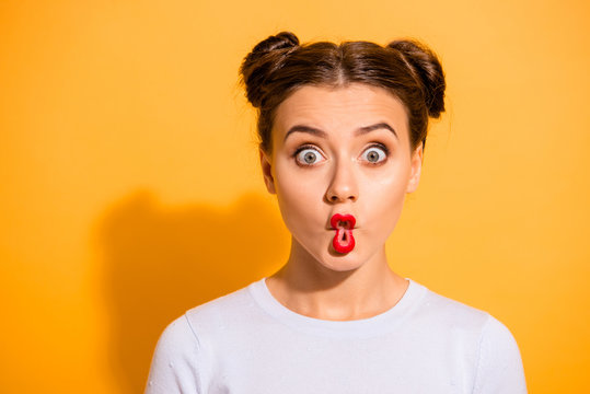 Close up photo beautiful she her lady pretty hairdo two buns big eyes fish-face foolish ridiculous hilarious idiotic facial expression wear casual white pullover clothes isolated yellow background