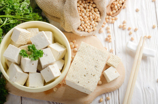 Soy Bean curd tofu in clay bowl and in hemp sack on white wooden kitchen table. Non-dairy alternative substitute for cheese. Place for text