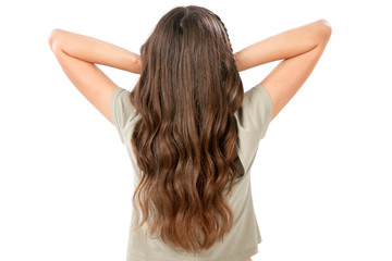 Rear view of a young woman with brown long hair. Isolated on white.