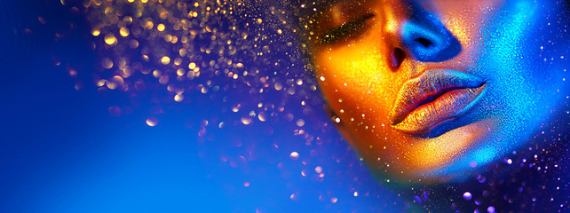 Fashion model woman face in bright sparkles, colorful neon lights, beautiful sexy girl lips. Trendy glowing gold skin make-up