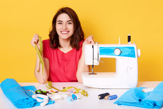 Close up portrait of charming woman seamstress sitting at table with sewing machine on yellow background in studio, dressmaker sews new dress, looks happy, holds measure tape, designer makes outfit.