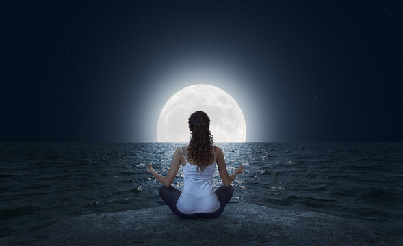 Young woman meditating on the beach at full moon
