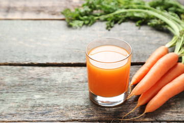 Wall Mural - Fresh carrot with glass of juice on grey wooden table