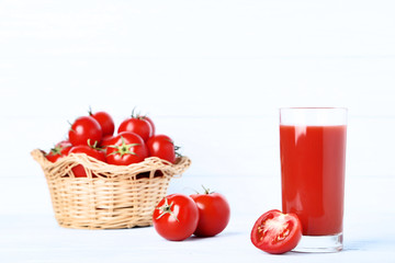 Wall Mural - Tomato juice in glass and basket on wooden table