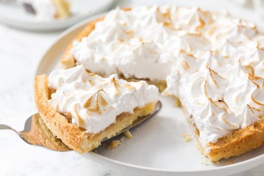 Slice of lemon meringue tart on a white plate