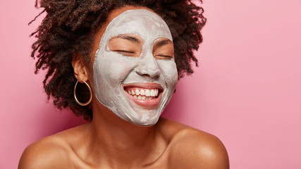 Close up portrait of happy delighted woman applies clay mask, closes eyes and smiles delightfully, imagines something pleasant, stands over pink background empty space on right side. Skin care concept Fototapete