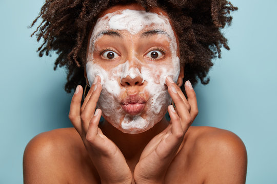 People, wellness, hygiene and skin problems concept. Lovely Afro American lady keeps lips folded, touches cheeks, has white foam on faces, washes with beauty gel, feels refreshed, has wide opened eyes
