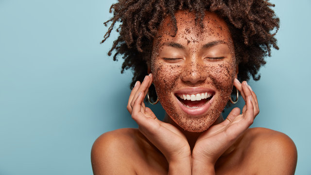 Cheerful dark skinned lady applies coffee scrub on face, pampers skin, closes eyes from pleasure, smiles positively has bare shoulders, stands against blue background, free space aside. Beauty concept