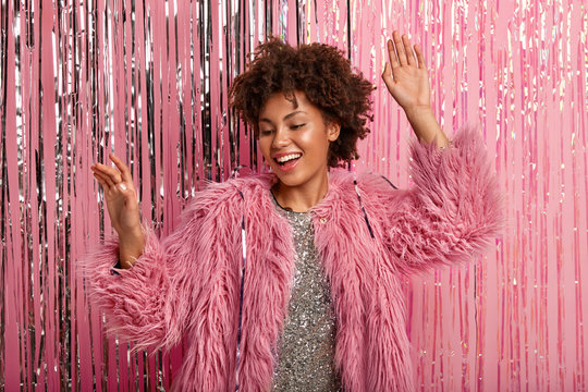 Studio shot of joyful Afro American woman laughs sincerely, feels relaxed, dances while listens favourite music, wears pink fur coat and sparkling dress, models over rosy background. Celebration