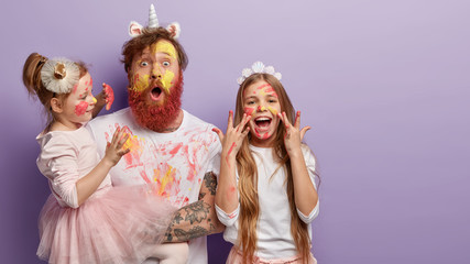 Horizontal shot of shocked dad has yellow face painted with watercolors, two children have fun with father, joyful expressions, isolated over purple background with free space for promotion. Wall mural