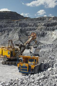 Heavy mining excavator loads rock ore into a dump-body large mining truck. Quarry equipment. Mining industry.