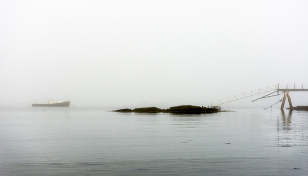 lobster boat in fog anchored with dock