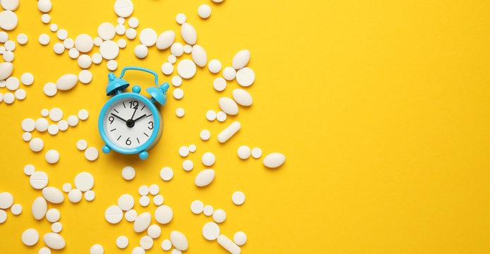 Sleeping pills and an alarm clock, insomnia concept. Trouble falling asleep.