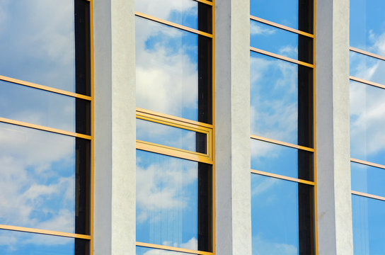 beautiful urban architecture background. window reflection of a clouds on a blue sky. perspective side view with three columns