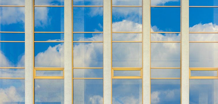 beautiful urban architecture panoramic background. window reflection of a clouds on a blue sky.