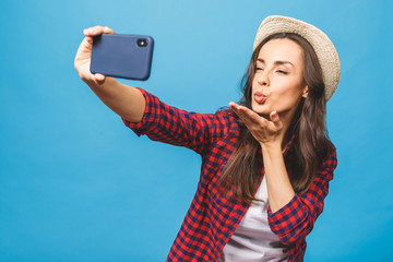 Travel concept! Charming young woman in white hat travel and take selfie on front camera smartphone isolated on blue background.