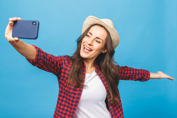 Charming young woman in white hat travel and take selfie on front camera smartphone isolated on blue pink background.