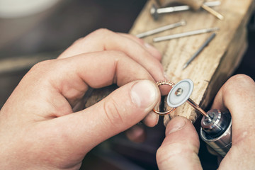 Jeweler polishes a gold ring with a special tool. Workflow in the workshop close-up.