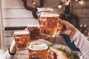 Group of friends making celebratory toast with beer
