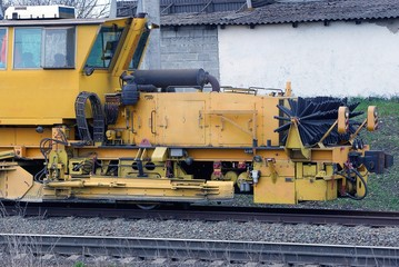 yellow repair locomotive stands on the rails of the railway