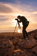 Men photographer on top of mountain at sunset background