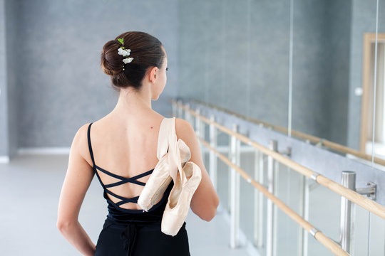 Ballerina with pointe shoes is finishing dance workout in ballet class room. Girl is standing back near barre and mirror.
