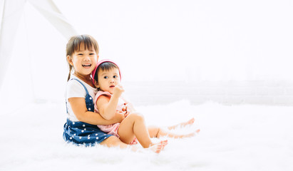 Happy childhood of two sister playing together in home. Concept picture for love and bonding in family.