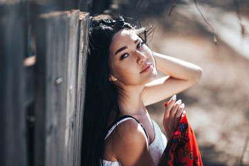 Portrait of a Beautiful black haired girl in a white vintage dress standing near wood fence.Young woman model posing in a russian national style . red shawl