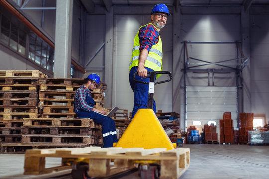 Male warehouse worker pulling a pallet truck