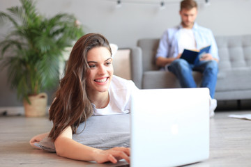 Smiling beautiful woman using laptop with blurred man in background at home.