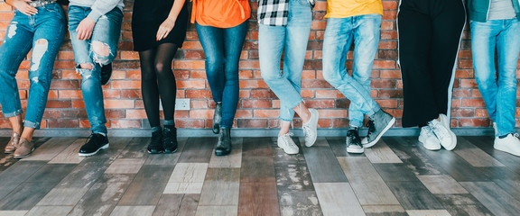 People diversity. Cropped shot of men women legs in jeans. Group standing leaning against brick wall. Relaxed millennials