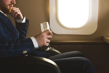 A young successful businessman in an expensive suit sits in the chair of a private jet with a glass of champagne in his hand and looks out the window
