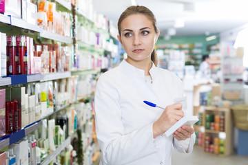 girl pharmacist is inventorying druggist