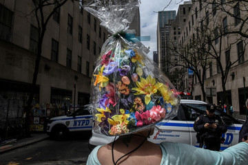A woman wears a bonnet near police cars during the annual Easter Parade and Bonnet Festival on Fifth Avenue in New York City